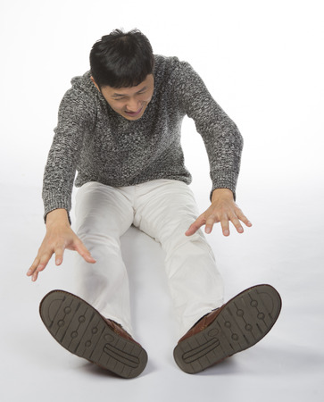 tough: Stiff man sits on floor and bend forward, shows tough expression