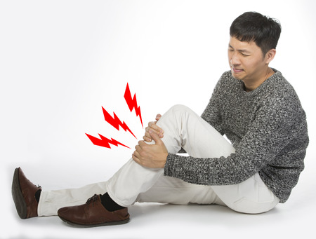 shin: Asian man suffering from shin pain, sits on the white floor