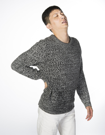 Back pain asian man, a man in casual clothes is suffering from pain with his right hand on waist