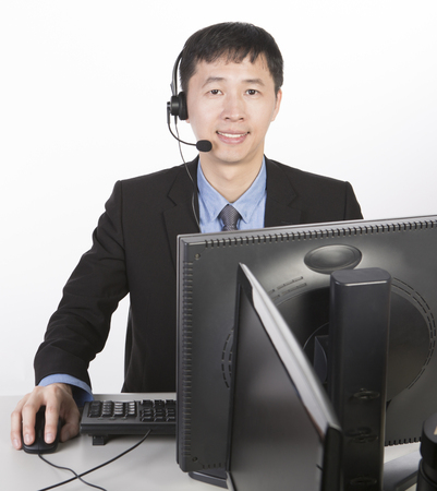 operator in black suit clicking mouse, white background Stock Photo