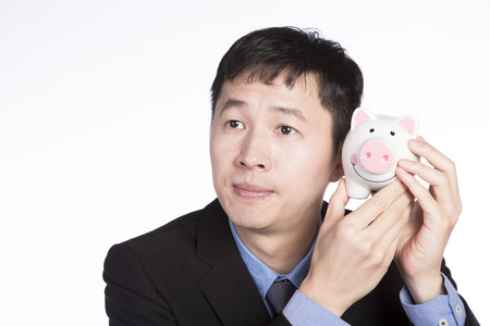 Asian businessman in black suit hearing to a piggy bank isolated on white background