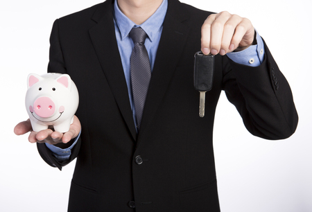 Businessman in black suit holding a piggy bank on right hand and a car key in his left hand isolated on white background