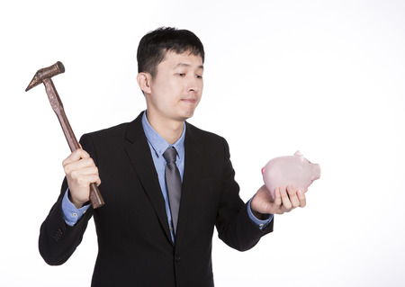 Businessman in black suit holding a hammer and gets ready to break down the piggy bank Stock Photo