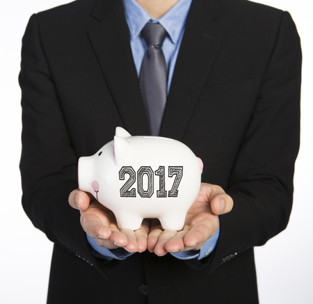 Businessman in black suit holding a piggy bank isolated on white background, 2017 words on the piggy bank