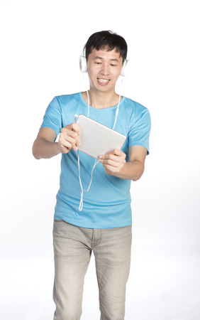 asian man with white earphone playing games on tablet, white background