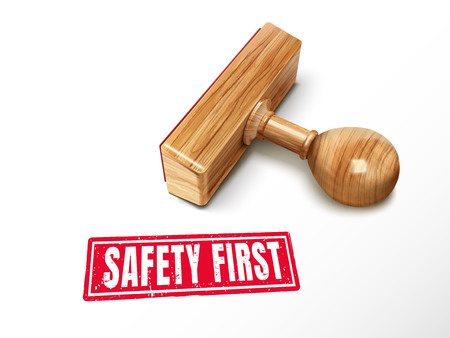 Safety First red text with lying wooden stamp, 3d illustration