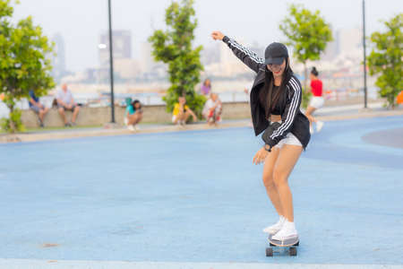 Asian woman playing surf skate or skates board outdoors on beautiful summer day. Happy young women play surf skate at park on morning time in the park.