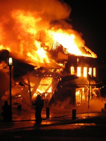 effondrement: Pompier lutte contre la maison en feu.