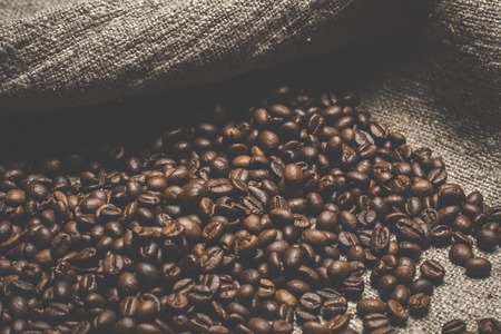 Coffee beans on vintage background, burlap sac Stock Photo