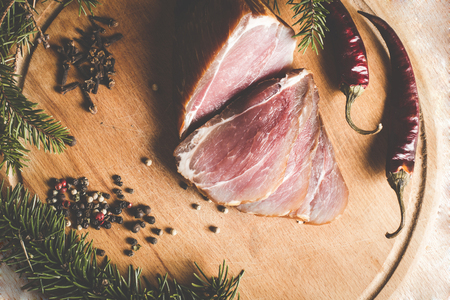 charcutería: smoked ham with pepper and cloves on a wooden board decorated with fir