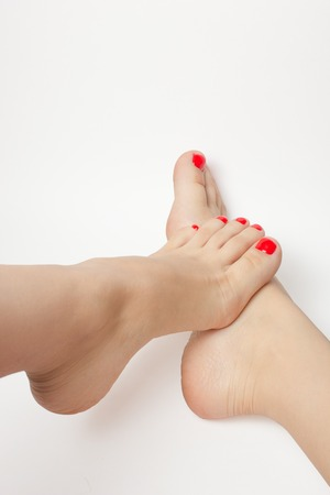footcare: Beautiful female feet with a pedicure red color. Isolated on white background