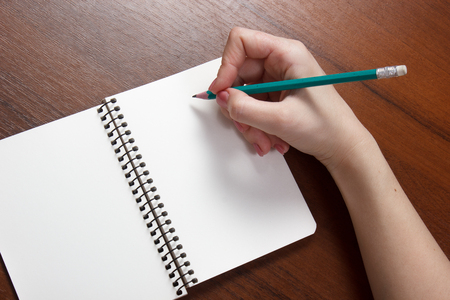 Closeup photo of girl writing in notebook with pencil Stock fotó