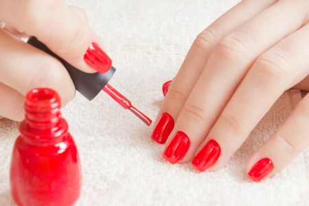 Manicure - Beautiful manicured womans nails with red nail polish on soft white towel. Stock Photo