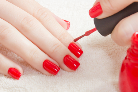 Manicure - Beautiful manicured womans nails with red nail polish on soft white towel. There is a bottle of red lacquer