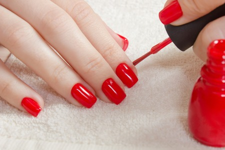 Manicure - Beautiful manicured womans nails with red nail polish on soft white towel. with a bottle of red lacquer