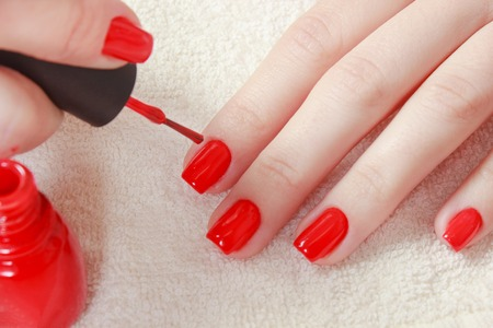 Beautiful manicured womans nails with red nail polish on soft white towel. Stock Photo