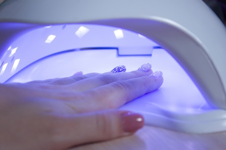 deposition: UV lamp gel polish manicure process in a beauty salon. Salon procedure. The master coats the clients nails with a varnish.