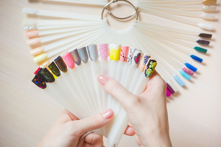 Top view woman selects yellow color shellac nail polish.Nail technician shows the color palette of nail services in beauty salon.