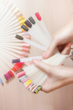 Hand and palette of colorful nails patterns. Nail technician shows the color palette of nail services in beauty salon store. spa treatments. beauty and fashion concept.