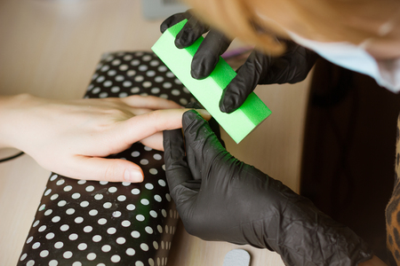 manicurist polishing index finger for manicure in nail beauty salon. Step of manicure process.