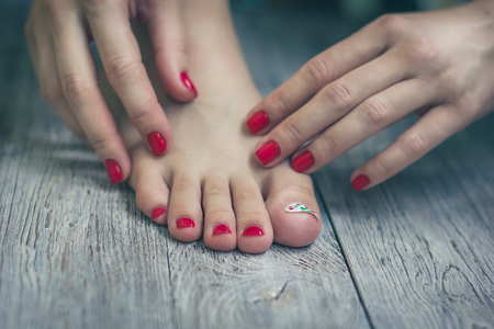 Red manicure and pedicure on vintage wooden background