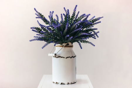 Bunch of fresh lavender in a basket on a white wall background