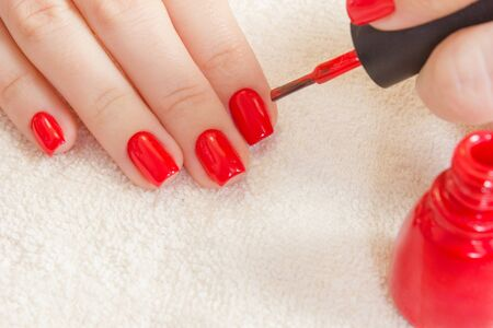 Girl paints her nails red nail polish. Beauty salon. manicured hand on white towel and red bottle gel laquer