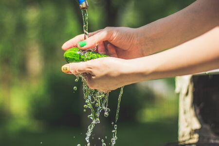 Washing the cucumbers in woman hands with water splash on the yard background