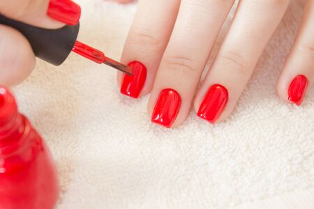 Manicure process. Nail polish being applied to hand, polish is a red color. Female hands