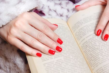 Young girls hands with red nails holding a book. Unrecognizable woman with fashion manicure in retro blanket reading book. Close up