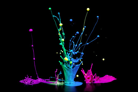 This is a colorful paint splash on a audio speaker isolated on a black background.