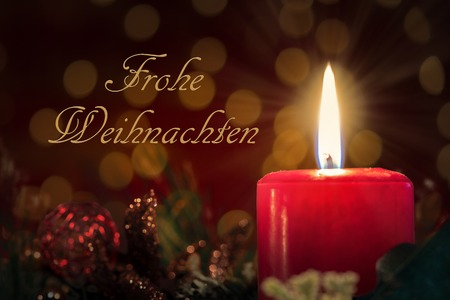 Christmas decoration with burning red candle. Blurred background and german text Frohe Weihnachten.