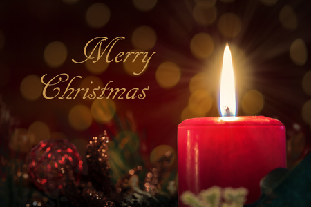 Christmas decoration with burning red candle. Blurred background and text with message merry christmas