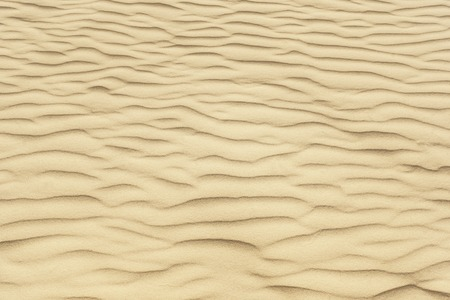 A texture of crystal clear sand with waves.