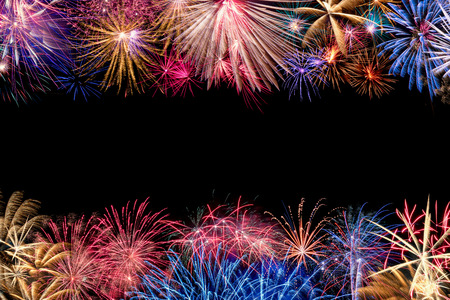 A very colorful border of different fireworks with copyspace in the middle of the image.