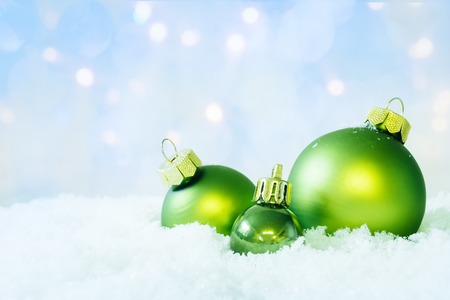 soft background: Three christmas balls on snow with soft bokeh background. Stock Photo
