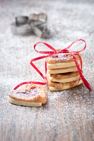 cookie cutter: Fresh cookies with icing sugar filled with jam an cookie cutter in the background.