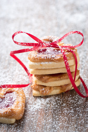 atmospheric: A pile of heart cookies on a rustic wooden table. You can use it for a greeting card or recipe.