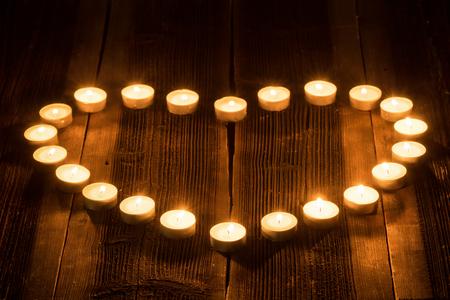 firing: Heart shaped firing candle on a wooden rustic desk.