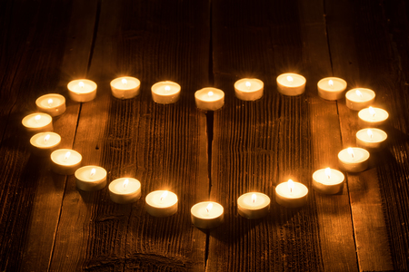 Herzförmige Brennen Kerze auf einem hölzernen rustikalen Schreibtisch. Standard-Bild - 50426918