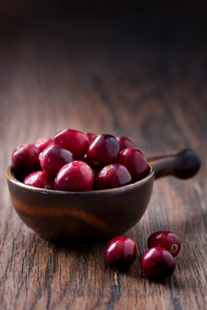 mountain cranberry: Fresh cranberries in a brown bowl on a rustic wooden table. Stock Photo