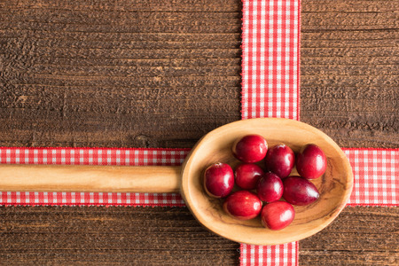 mountain cranberry: Rustic background with cranberries on a wooden spoon. Stock Photo