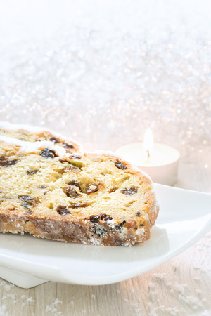 Fresh Christmas Stollen on a white plate with candle
