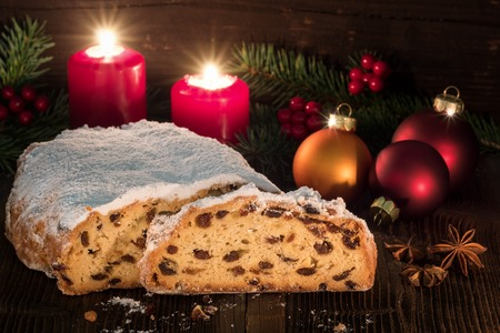 Christmas Stollen on a table with a rustic Background and candlelight.