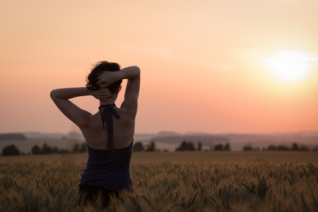 Young women in wheat field looking at Sunset