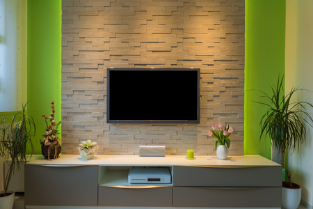Modern living room interior - tv mounted on brick wall with black screen and ambient light.