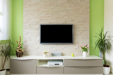 Modern living room interior - tv mounted on brick wall with black screen. Stock Photo