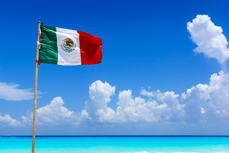 Mexican national flag flying in the wind on an amazing sandy beach in front of turquoise water of the caribbean sea, near Cancun, Mexico