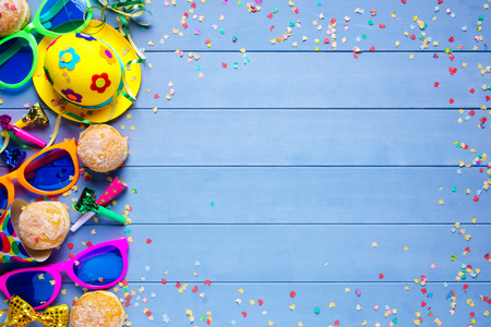 Colorful birthday or carnival border with party items on blue wooden background Stock Photo