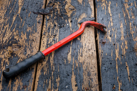 One iron nail and nail puller on a wooden background.. Stock fotó